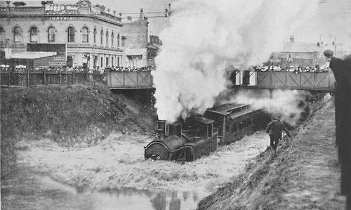 Flooded railway tracks with train passing under the bridge that crosses Chapel Street, near Arthur and Palermo Street.  25 January 1907.  Photo from the Stonnington History Centre's online photo collection (Reg no. PH 491)